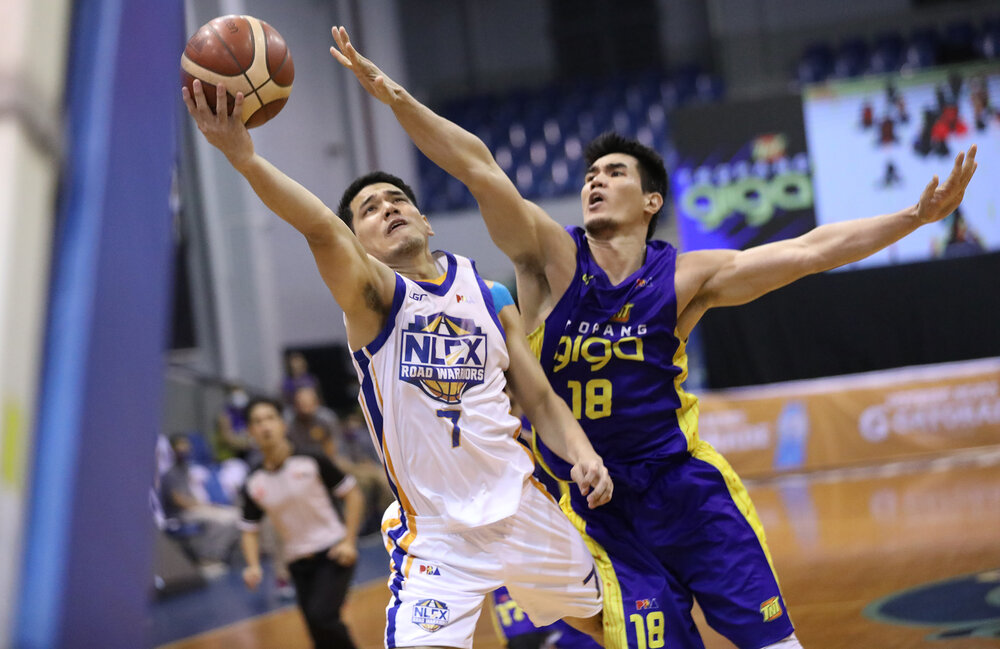 NLEX's Kevin Alas eludes the defense of TNT's Troy Rosario. (Photo from PBA)