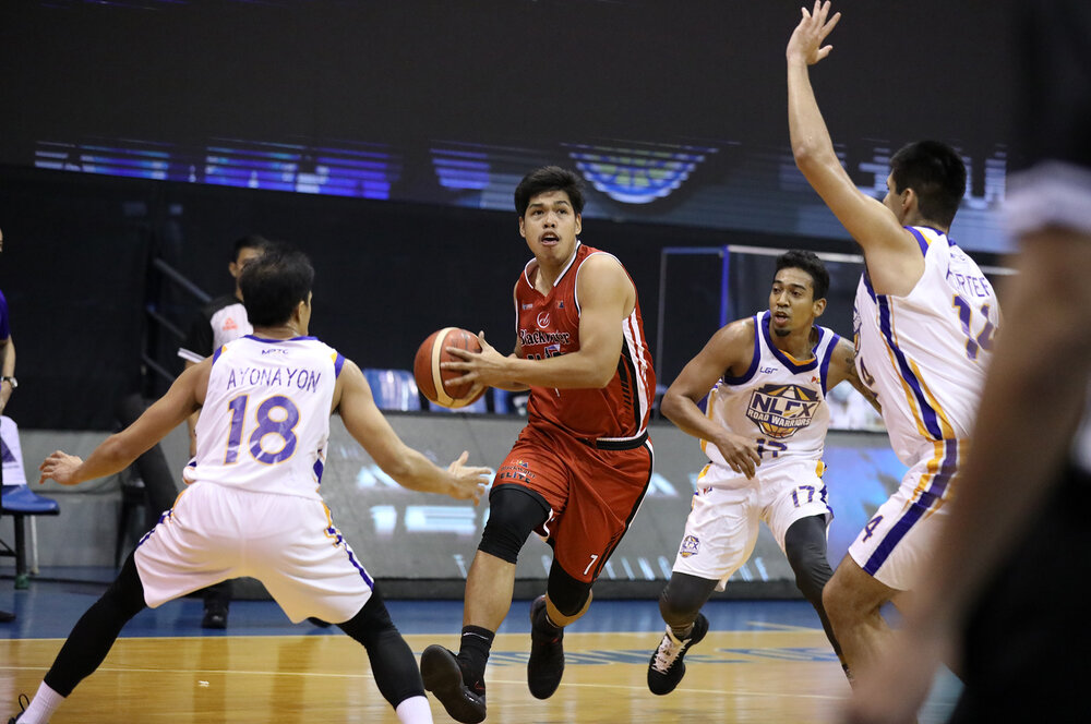 Don Trollano steps past Mike Ayonayon and Kenneth Ighalo of NLEX. (Photo from PBA)