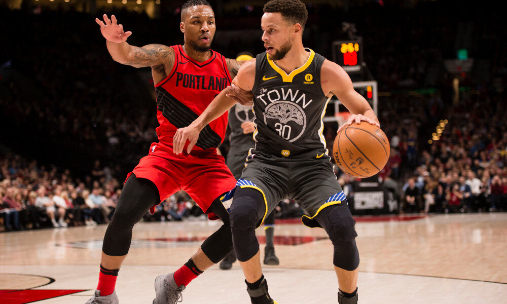 Warriors' Stephen Curry protecting the ball from Damian Lillard of the Blazers. (Photo via USA TODAY Sports)